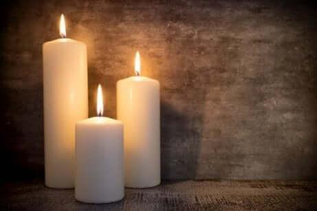 3 hvite stearinlys som brenner