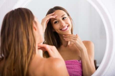 En kvinne som driver med hudpleie foran speilet.