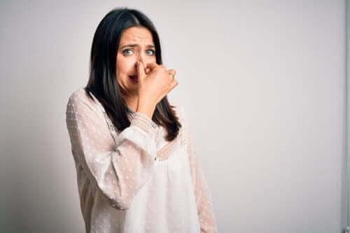 En kvinne som holder seg for nesen