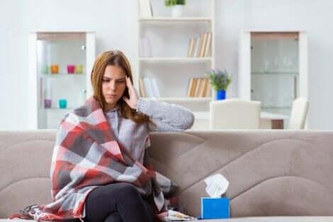 En forkjølet kvinne innpakket i et teppe med en boks med papir ved siden av seg.