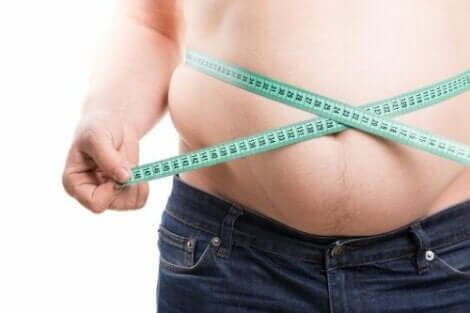 En overvektig mann som måler midjen sin.