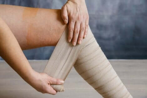 En person som tar på seg kompresjonsbandasjer på grunn av tunge ben.