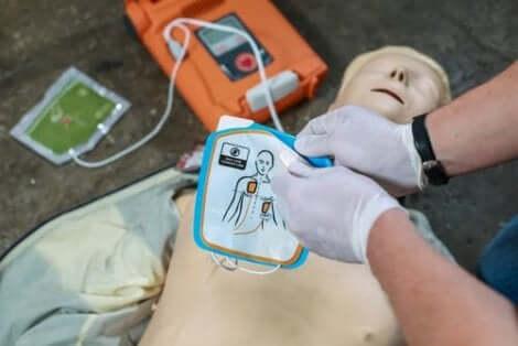 En som bruker defibrillator på en øvelsesdukke for hjertestans.