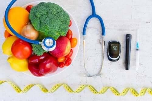Instrumenter for diabetespleie ved siden av en bolle med frukt og grønnsaker.
