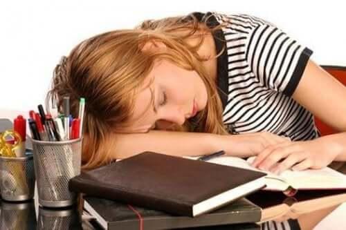 Kvinne med høyt ferritin som sover på skrivebordet.