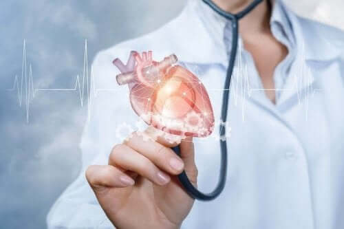 Lege som holder opp stetoskop med hjerte på enden.
