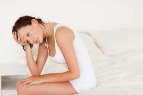 Kvinne i hvitt som sitter i sengen som behandler urinveisinfeksjoner tidlig for å unngå komplikasjoner.