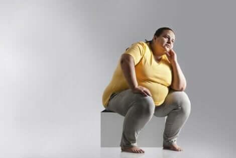Overvektig kvinne som sitter på en boks med en dårlig kroppsholdning.