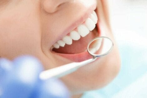 Tannlege sjekker tenner med speil.