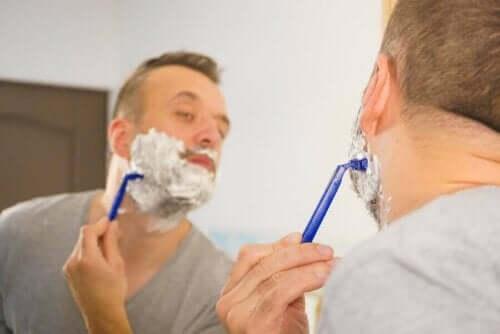 En mann som barberer seg i speilet