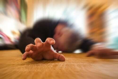 Mann på gulvet som opplever et epileptisk anfall