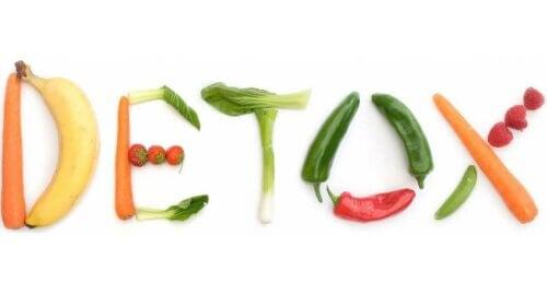 """Frukt og grønnsaker lagt på en hvit bakgrunn for å stave """"DETOX"""""""