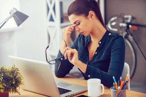 Kvinne på kontoret foran laptop står overfor daglig stress.