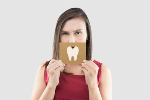 Kvinne som holder et skilt med en tann med et karies på foran munnen