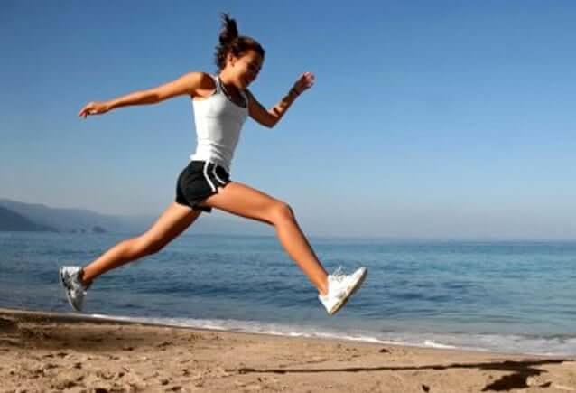 En kvinne som hopper på stranden