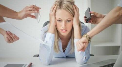 Stresset kvinne som lener seg på skrivebordet med hodet mellom hendene med flere mennesker som viser henne forskjellige ting