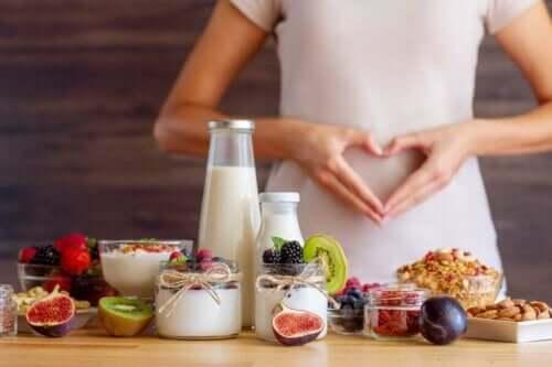 Kvinne som lager hjerte med hendene over magen bak mat som yoghurt, frukt og nøtter