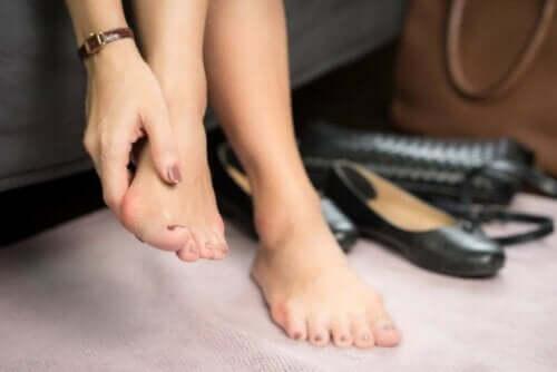 En kvinne masserer føttene