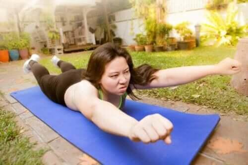 En kvinne trener mot skoliose i hagen