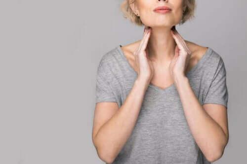En kvinne som berører nakken sin.