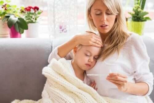 En mor som prøver å redusere datterens feber.