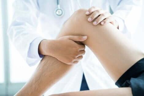 En lege sjekker pasientens ben