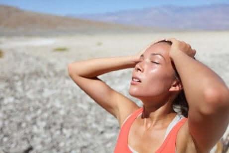En jente som nyter solen på stranden for å holde huden hydrert.