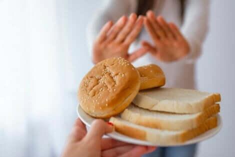 En kvinne som avviser en tallerken med brød.