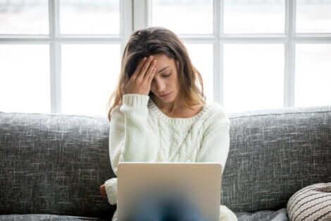 En kvinne som opplever stress mens hun jobber på den bærbare datamaskinen på sofaen.