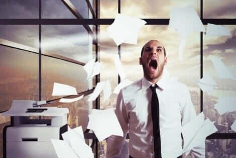 En mann som har et nervesammenbrudd på jobben og kaster papir i luften.