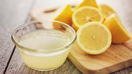 Sitronsaft og sitroner som står på en kjøkkenbenk.
