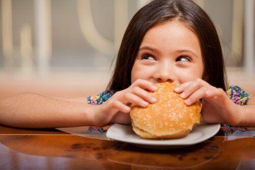 Jente som spiser burger.