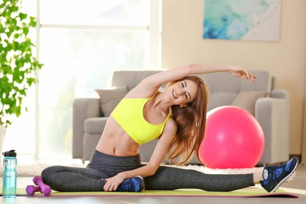 kvinne som strekker seg på en yogamatte