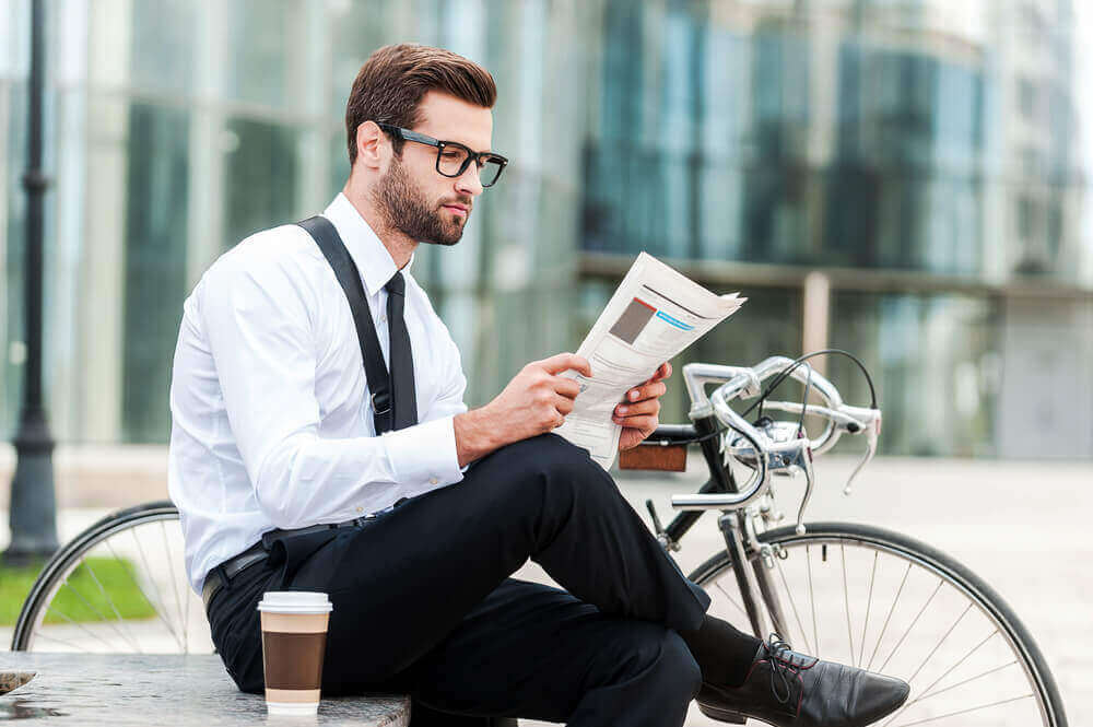 mann med briller som leser en rapport