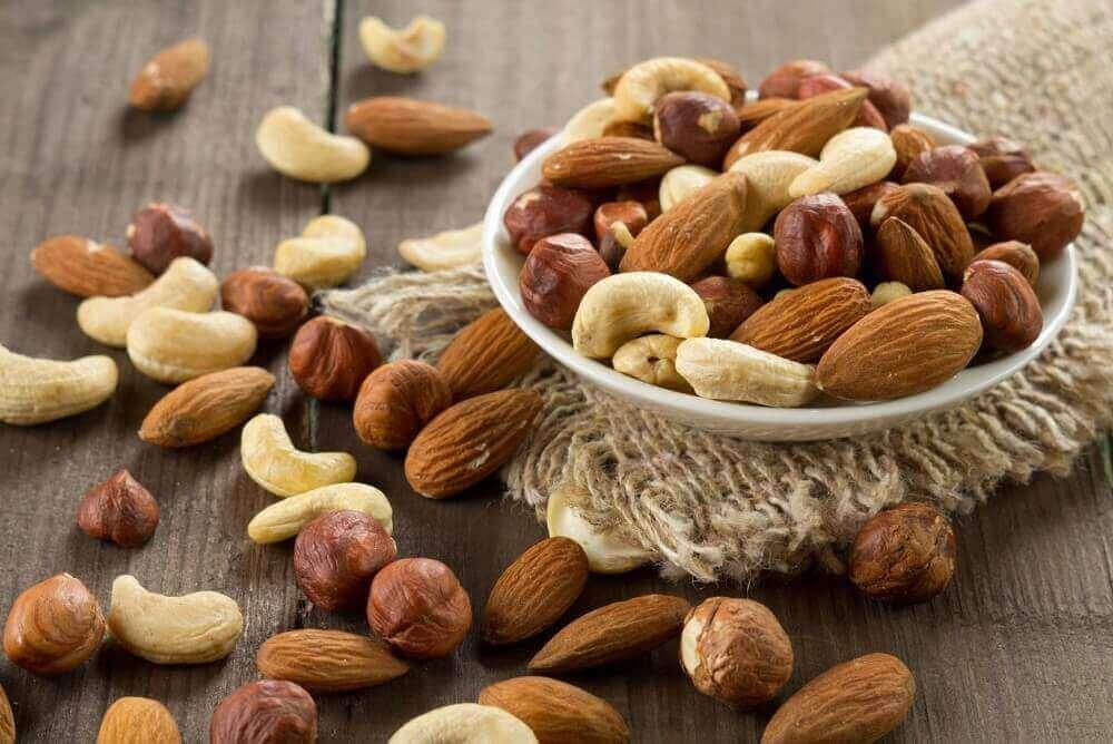 Skål med nøtter på et bord, nøtter øker det gode kolesterolet