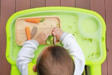 En baby som spiser grønnsaker.