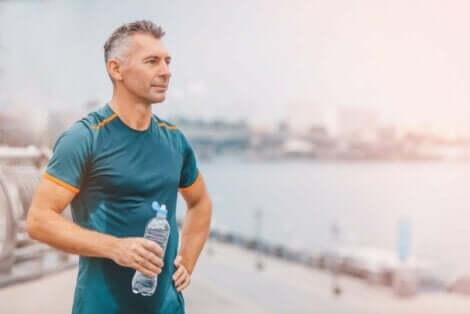 En eldre mann som drikker vann etter en løpetur.