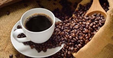 En kaffekopp med kaffebønner som ligger rundt
