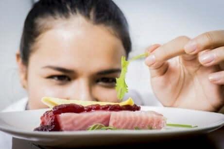 En kvinne pynter en tallerken med fisk.