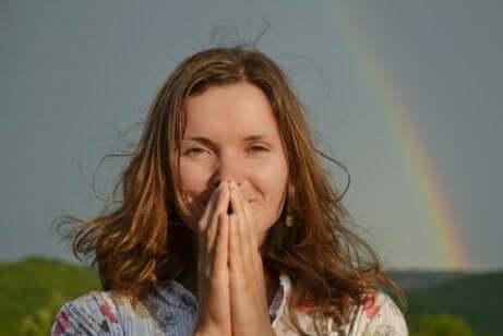 En kvinne som ber foran en regnbue.