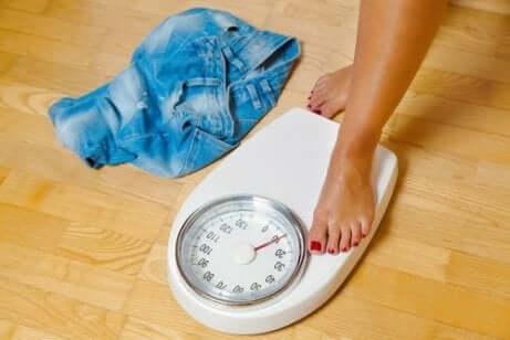En kvinne som har foten på vekten