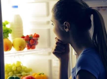 En kvinne som ser på frukt og melk i kjøleskapet om natten.