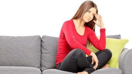 En kvinne som sitter på en sofa, opprørt.