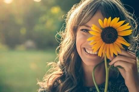 En lykkelig kvinne og en solsikke.