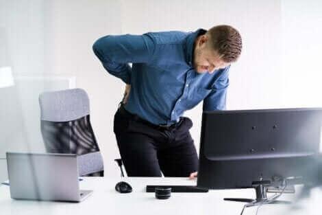 En mann som står bøyd over skrivepulten med skiveprolaps