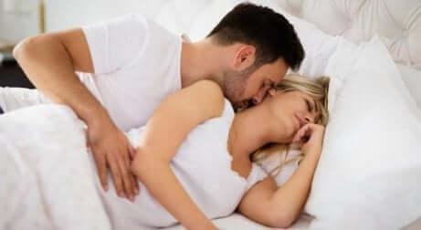 Et par som ligger i sengen.