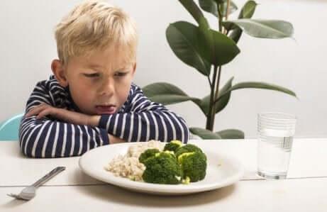 et barn som rynker på nesen av brokkoli