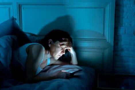 Kvinne på telefonen i et mørkt rom.