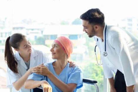 To leger som snakker med en kvinnelig kreftpasient som sitter i rullestol.