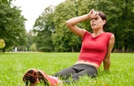 en kvinne som sitter på gresset etter trening